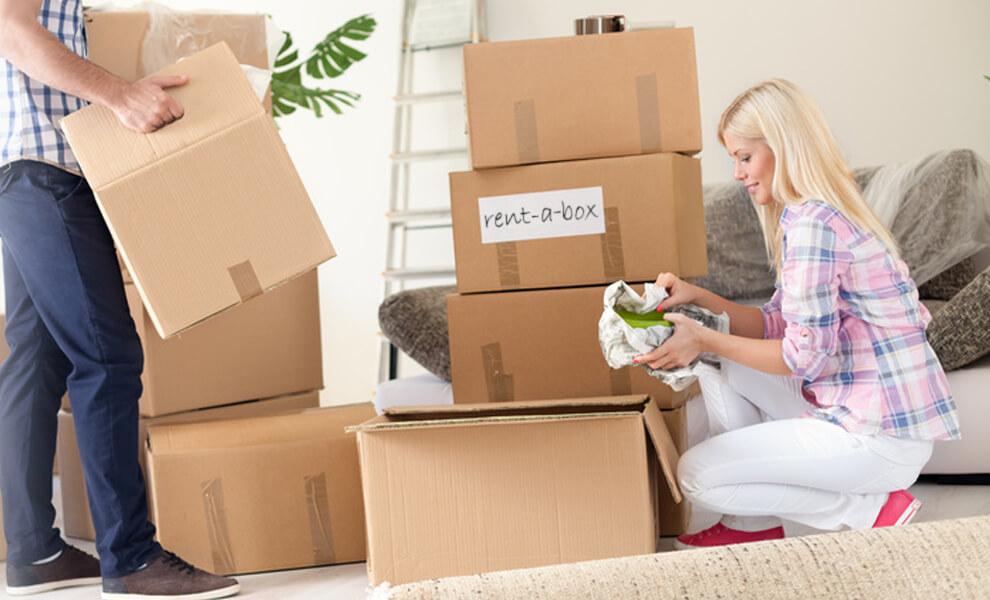 femme emballe affaires privés pour déménagement cartons stockages garde-meuble